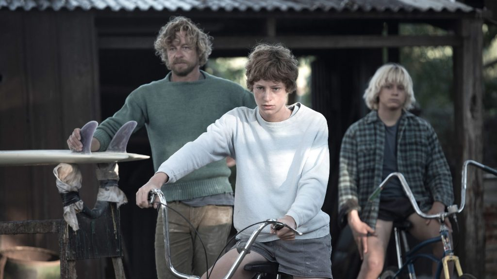 A man and two boys on bicycles